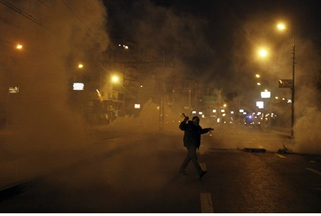 Protester flees from tear gas in front of the