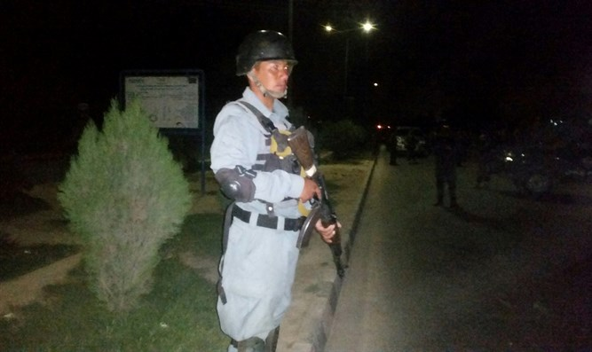 Afghani policeman stands guard outside of American University following terror attack
