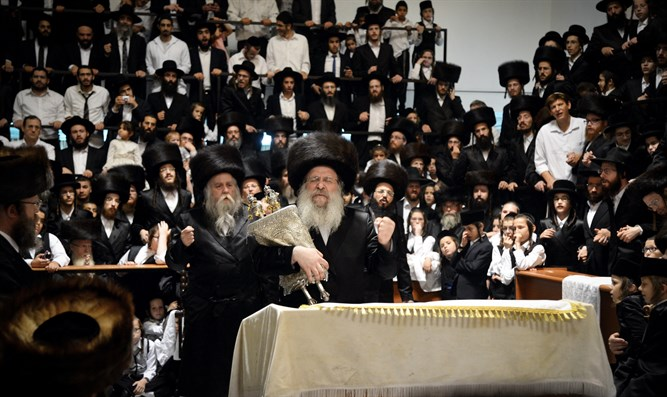 Jewish men of Chasidic Nadvorna dynasty carry Torah scroll on Simchat Torah